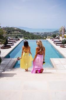 Deux demoiselles d'honneur en robes colorées lumineuses jaune et rose au bord de la piscine avec des bouquets avec une magnifique vue tropicale sur la mer à la villa