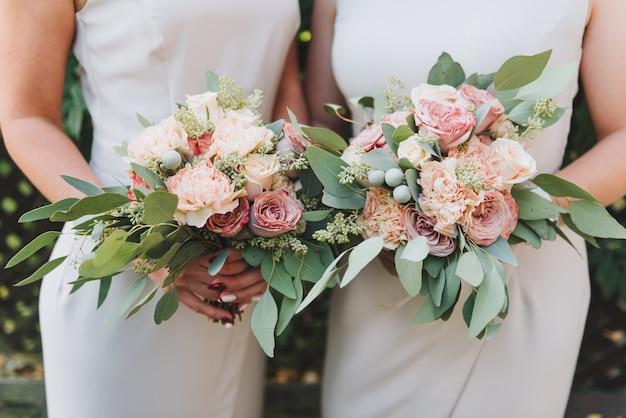 Deux demoiselles d'honneur tenant leurs bouquets de pivoines et d'eucalyptus