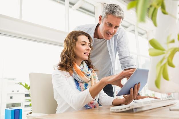 Deux designers occasionnels travaillant avec tablette au bureau