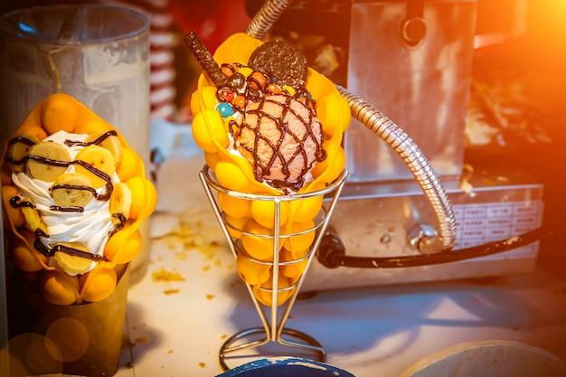 Deux desserts crème glacée avec banane et biscuits sur la table gaufre de hong kong sur la table