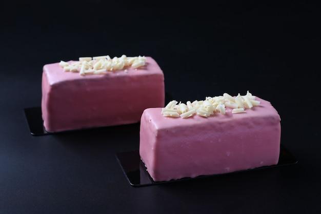 Deux desserts mousse avec biscuit aux amandes, coolie à la fraise et mousse aux fraises recouvert de glaçage au chocolat rose gourmet sur fond noir. fermer