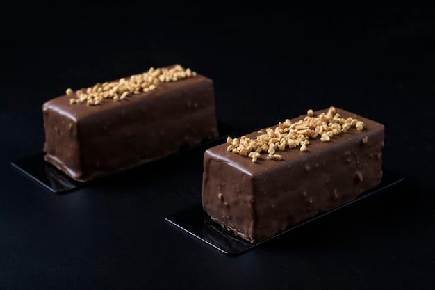 Deux desserts à la mousse avec praliné aux noisettes, chocolat au lait et glaçage aux noix de chocolat gourmet sur un fond noir gros plan.