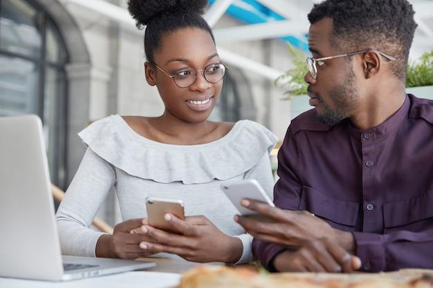 Deux directeurs de bureau féminins et masculins à la peau foncée, vérifient les notifications sur les téléphones portables, tiennent une réunion informelle, discutent de quelque chose