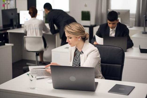 Deux directeurs de librairie travaillant sur un ordinateur portable dans un grand bureau lumineux. code vestimentaire professionnel