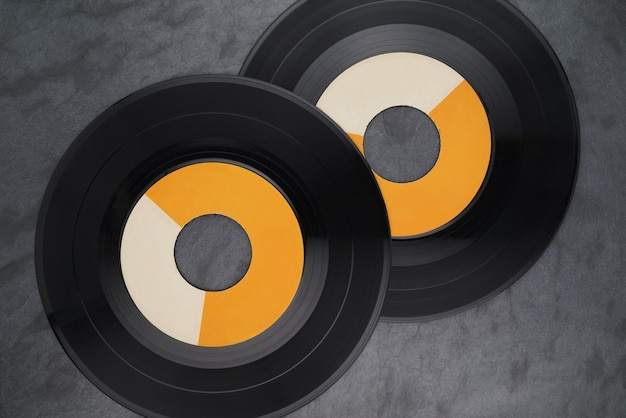 Deux disques vinyles simples de 7 pouces à large trou sur une surface en ardoise noire. vue de dessus