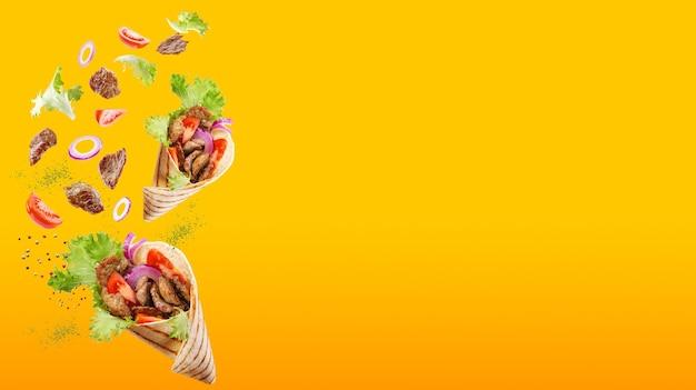 Deux döner kebabs ou shawarmas flottant avec des ingrédients isolés sur fond orange dégradé