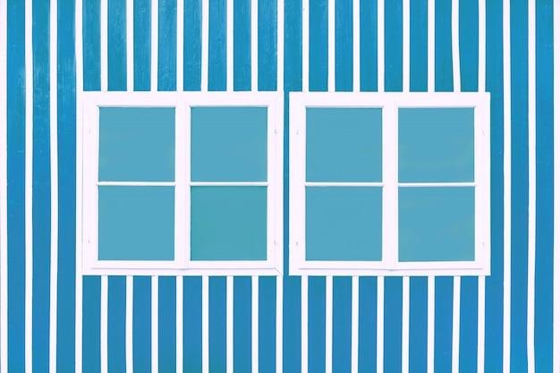 Deux doubles fenêtres blanches sur un mur bleu avec des lattes blanches.