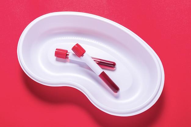 Deux échantillons de sang dans un bol de médecine blanc