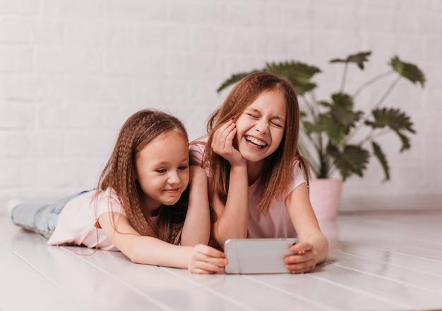 Deux écolières heureuses regardent une vidéo sur leur téléphone et rient