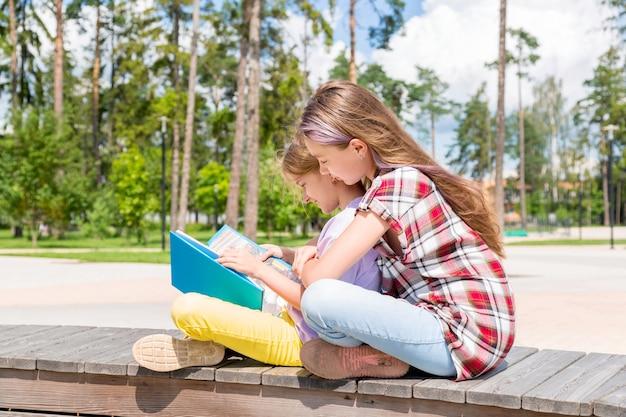 Deux écolières sont assises sur un banc dans le parc, font leurs devoirs, lisent un livre