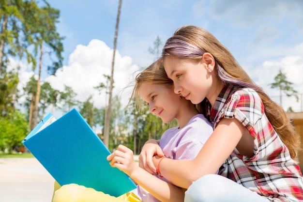 Deux écolières sont assises sur un banc dans le parc, font leurs devoirs, lit un livre