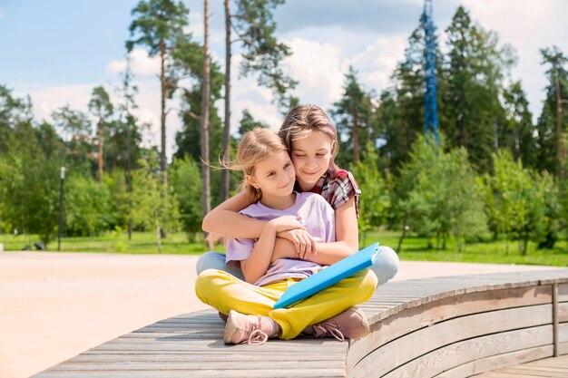 Deux écolières sont assises sur un banc dans le parc, se serrant dans les bras
