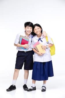 Deux écoliers asiatiques souriants avec de la papeterie colorée,