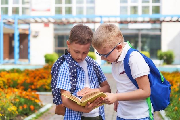 Deux écoliers mignons vérifient leurs devoirs dans le parc près de l'école.