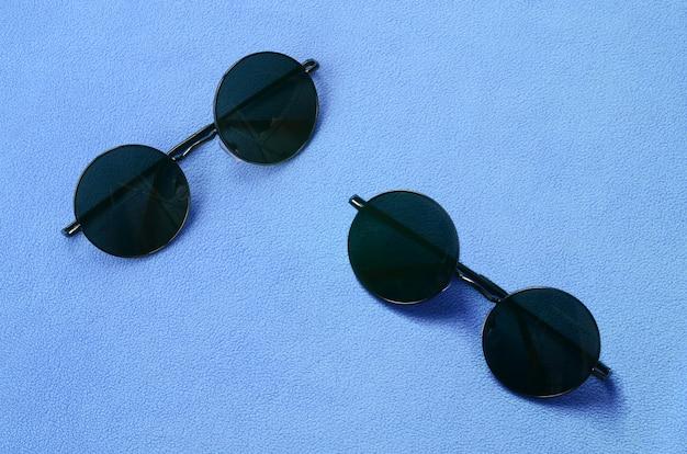 Deux élégantes lunettes de soleil noires à lunettes rondes reposent sur une couverture en molleton bleu clair doux et moelleux.