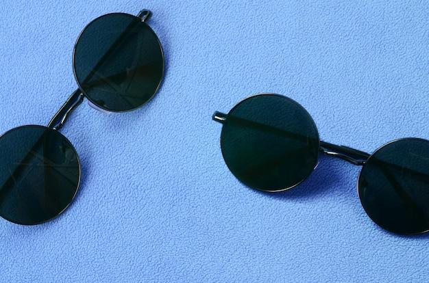 Deux élégantes lunettes de soleil noires avec des lunettes rondes se trouve sur une couverture