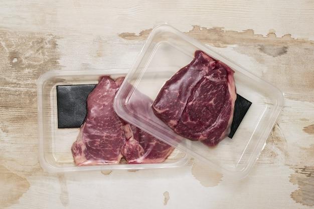 Deux emballages sous vide avec des steaks de boeuf sur une table en bois. emballage scellé pour la viande.