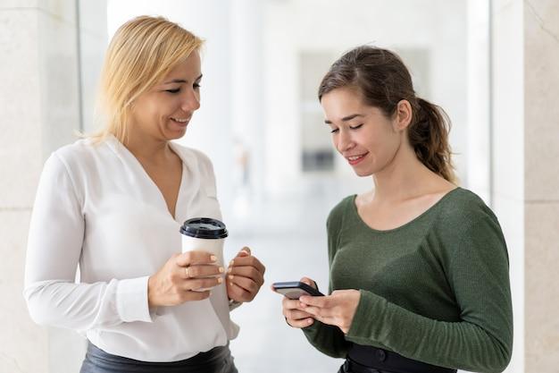 Deux employés de bureau consultent sur l'internet mobile