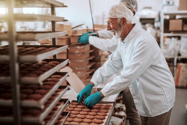 Deux employés caucasiens dévoués et assidus vêtus d'uniformes blancs stériles collectent et emballent des biscuits dans des boîtes. intérieur de l'usine alimentaire.