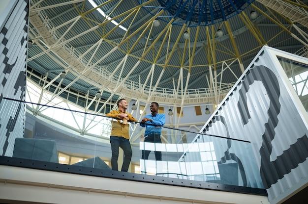 Deux employés discutant sur le balcon du bureau informatique