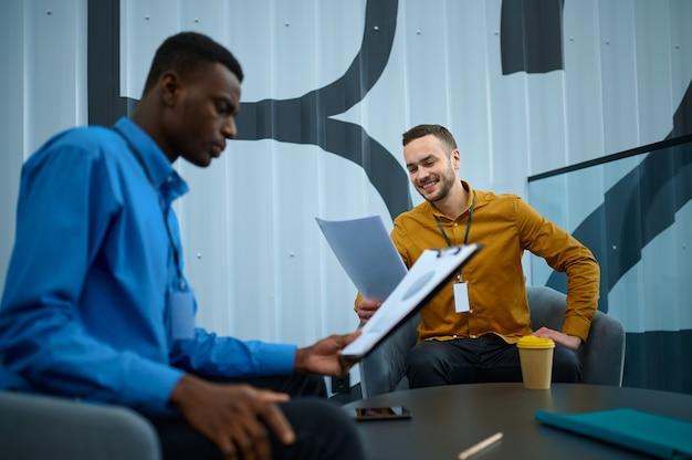 Deux employés masculins, conférence au bureau informatique. travail d'équipe et planification professionnels, remue-méninges de groupe, intérieur d'entreprise moderne en arrière-plan
