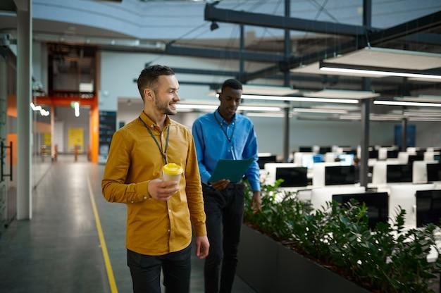 Deux employés masculins, réunis dans un bureau informatique. travail d'équipe et planification professionnels, remue-méninges de groupe, intérieur d'entreprise moderne en arrière-plan