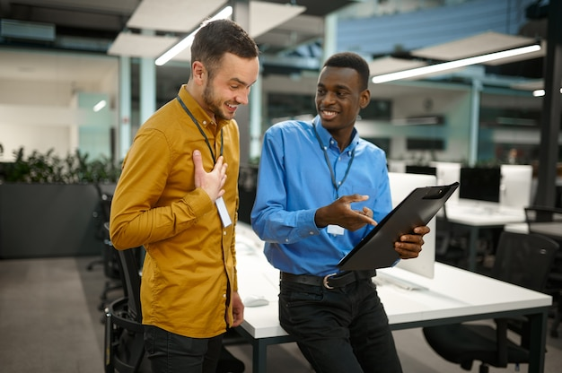 Deux employés masculins, se réunissant dans le bureau informatique