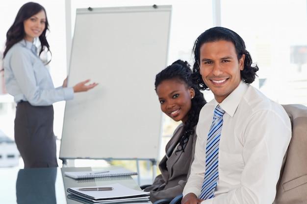 Deux employés souriants assis à un bureau dans une salle de réunion lors d'une présentation