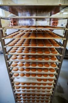 Deux employés d'usine alimentaire poussant des plateaux avec des biscuits frais. intérieur de l'usine alimentaire.