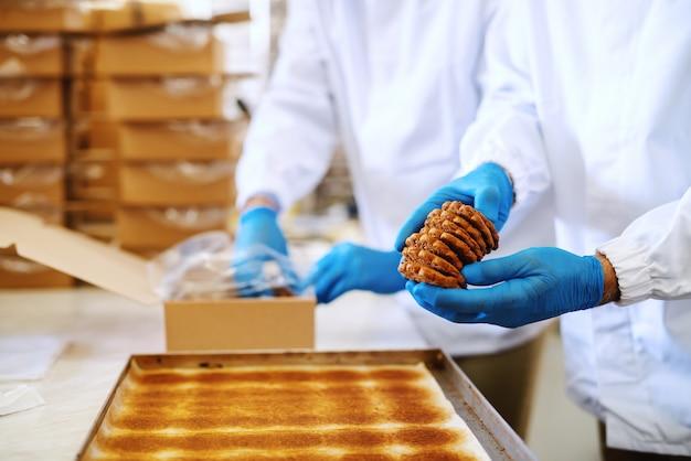 Deux employés d'usine alimentaire travaillant dur en uniformes stériles emballant des biscuits dans des boîtes.
