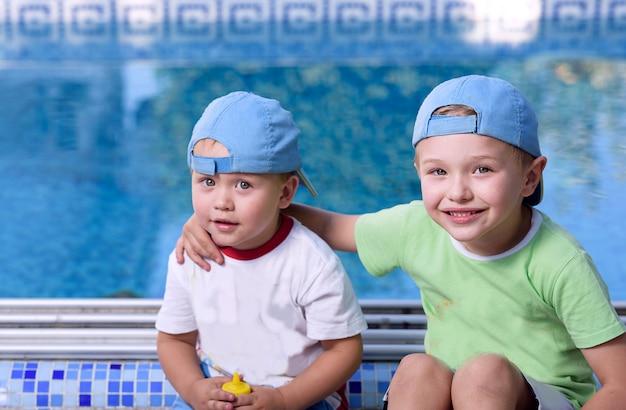 Deux enfants adorables frères et soeurs étreindre et s'amuser à la piscine