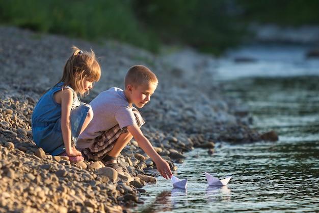 Deux enfants blonds mignons, garçon et fille sur la rive du fleuve envoyant des bateaux en papier blanc