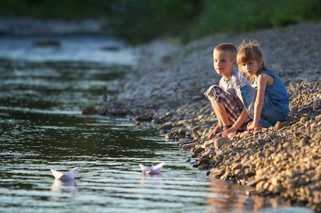 Deux enfants blonds mignons, garçon et fille sur la rive du fleuve envoyant dans l'eau des bateaux en papier blanc sur l'été lumineux