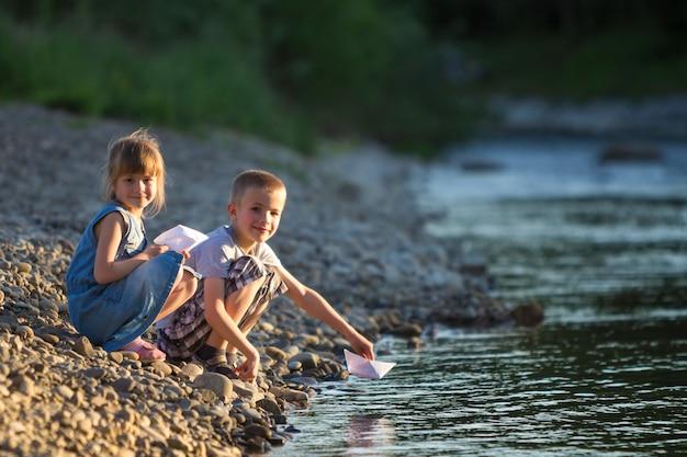 Deux enfants blonds mignons, garçon et fille sur la rive du fleuve envoyant dans l'eau des bateaux en papier blanc