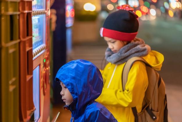 Deux enfants choisissent des boissons au distributeur automatique