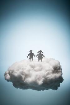 Deux enfants debout sur un nuage blanc.