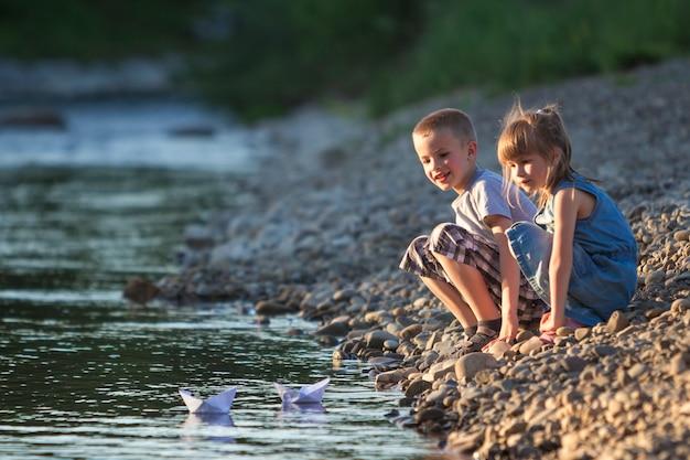 Deux enfants envoyant des bateaux en papier blanc avec de l'eau.