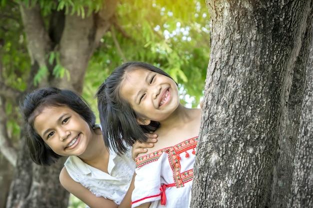 Deux enfants de fille mignonne asiatique souriant dans un parc