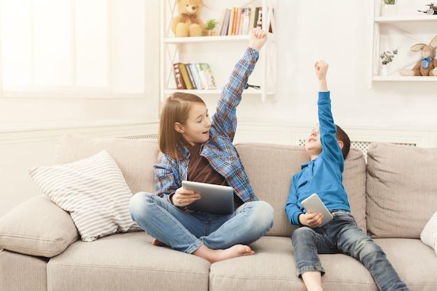 Deux enfants avec des gadgets sur un canapé à la maison