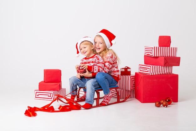 Deux enfants, un garçon et une fille en pulls et chapeaux santa assis sur un traîneau pour transporter des cadeaux. studio, fond blanc, espace pour le texte