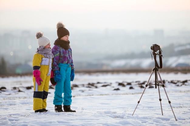 Deux enfants garçon et fille s'amusant dehors en hiver jouant avec un appareil photo sur un trépied sur un terrain couvert de neige.