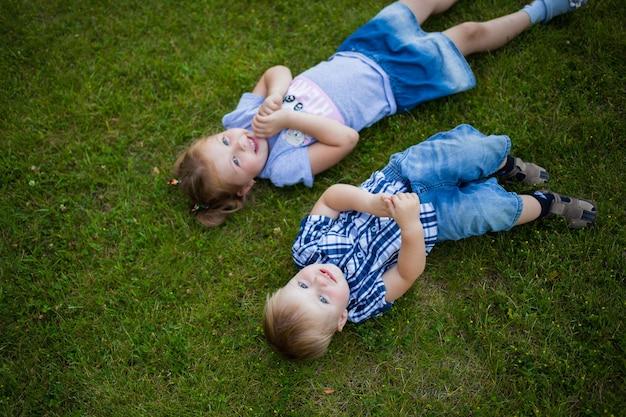 Deux enfants heureux riant garçon et fille se trouvent sur l'herbe les enfants jouent à l'extérieur