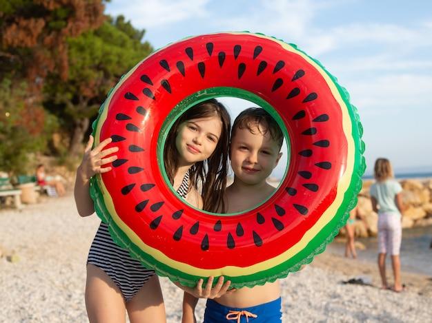 Deux enfants heureux tiennent un cercle de natation sur la plage de l'adriatique se