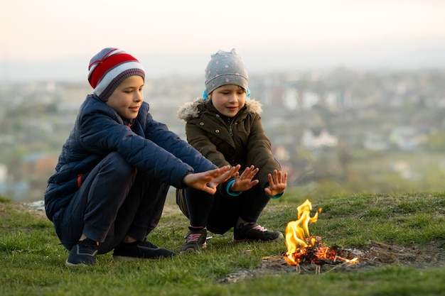 Deux enfants jouant avec le feu à l'extérieur par temps froid.
