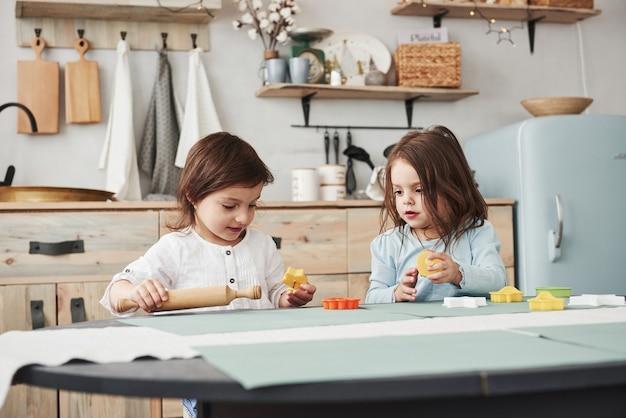 Deux enfants jouant avec des jouets jaunes et oranges dans la cuisine blanche.