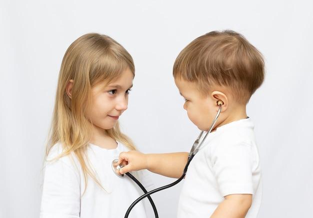 Deux enfants jouent au docteur sur fond blanc