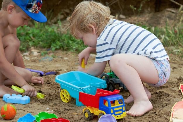 Deux enfants jouent dans le sable avec des jouets en plastique