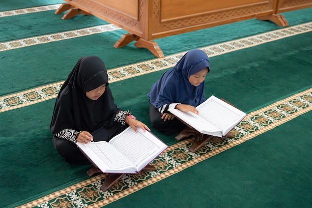 Deux enfants lisent le saint coran