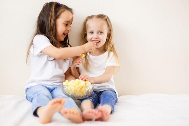 Deux enfants mangent du maïs soufflé sur le fond blanc