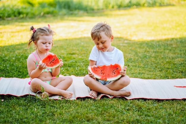 Deux enfants mangent de la pastèque dans le jardin. les enfants mangent des fruits à l'extérieur. collation saine pour les enfants. les tout-petits, fille et garçon, apprécient la pastèque